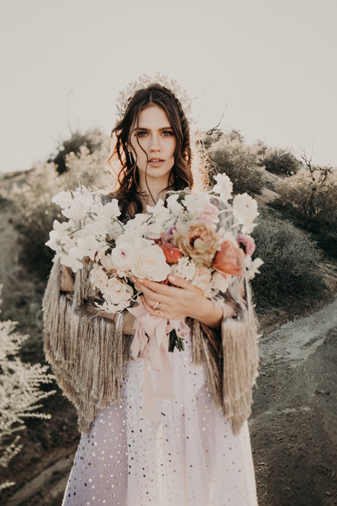 Rim-Rock-Ranch-Shoot-bride-alone-looing-at-camera-with-flowers-bride-wearing-a-sheer-gown-with-crystals-in-it-with-flutter-sleeves-and-a-crown