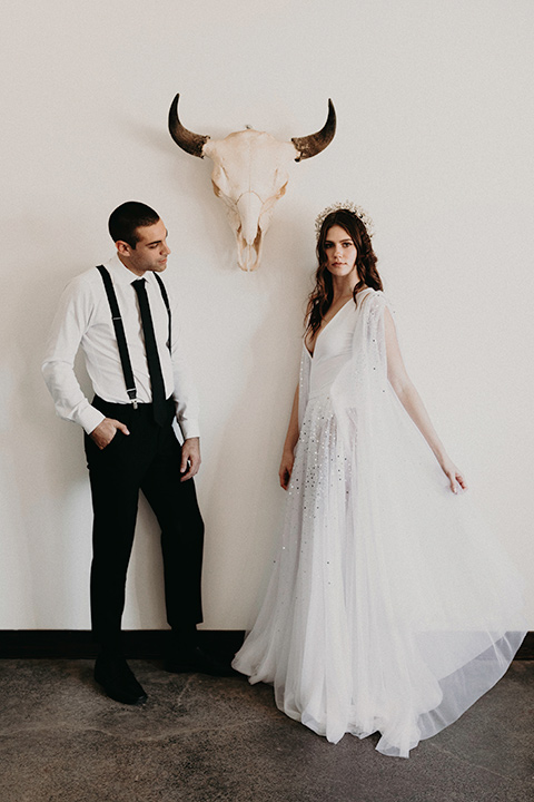 Rim-Rock-Ranch-Shoot-bride-and-groom-by-longhorn-skull-bride-wearing-a-sheer-gown-with-crystals-in-it-with-flutter-sleeves-and-a-crown-groom-in-a-white-shirt-black-pants-and-black-suspenders