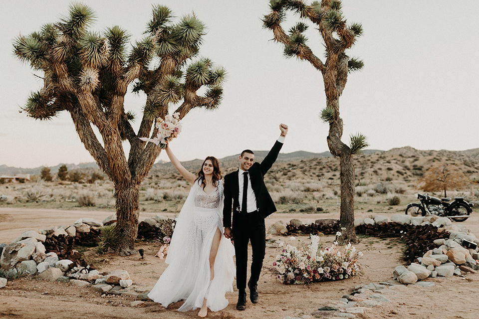 Rim-Rock-Ranch-Shoot-bride-and-groom-in-ceremony-space-with-hands-in-the-air-bride-in-a-bohemian-style-dress-with-a-sheer-overlay-and-crown-groom-in-a-simple-black-suit-and-long-tie