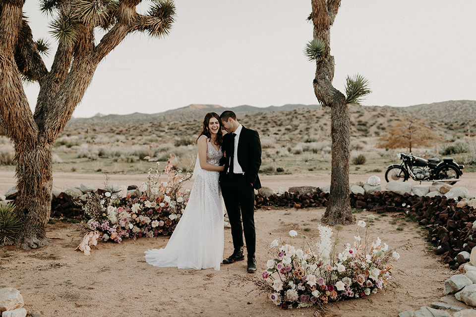 Rim-Rock-Ranch-Shoot-bride-and-groom-laughing-in-ceremony-space-bride-in-a-bohemian-style-dress-with-a-sheer-overlay-and-crown-groom-in-a-simple-black-suit-and-long-tie