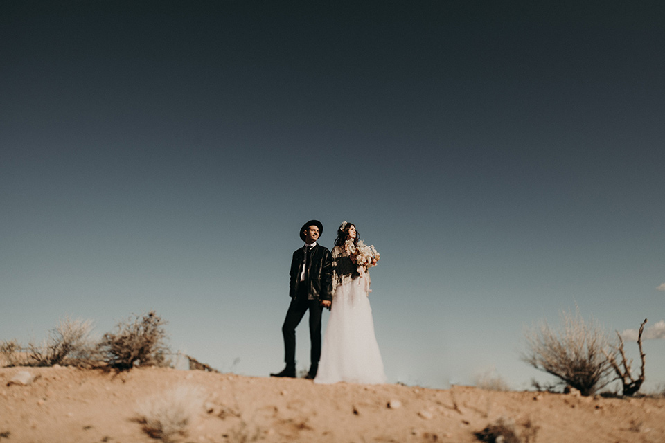 Rim-Rock-Ranch-Shoot-bride-and-groom-on-hilltop-with-hat-on-bride-in-a-bohemian-style-dress-with-a-sheer-overlay-and-crown-groom-in-a-simple-black-suit-and-long-tie
