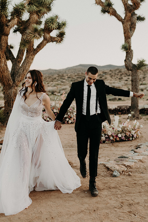 Rim-Rock-Ranch-Shoot-bride-and-groom-walking-bride-wearing-a-sheer-gown-with-crystals-in-it-with-flutter-sleeves-and-a-crown-groom-in-a-white-shirt-black-pants-and-black-suspenders