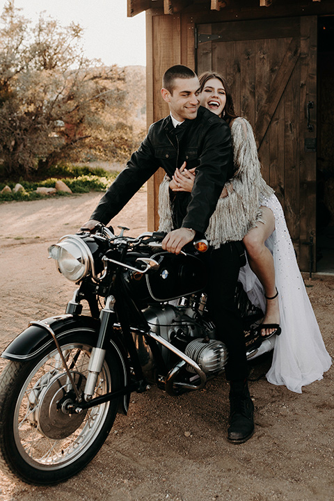 Rim-Rock-Ranch-Shoot-bride-laughing-on-motocycle-groom-steering-bride-wearing-a-sheer-gown-with-crystals-in-it-with-flutter-sleeves-and-a-crown-groom-in-a-white-shirt-black-pants-and-black-suspenders