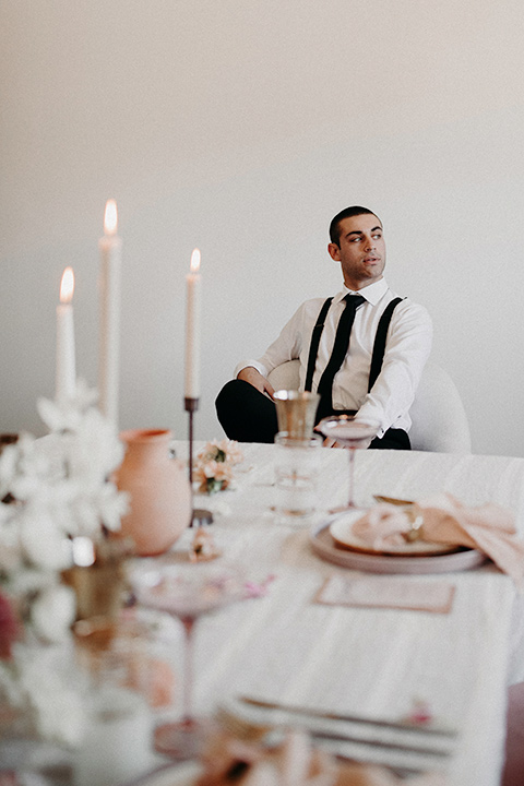 Rim-Rock-Ranch-Shoot-groom-sitting-at-table-groom-in-a-white-shirt-black-pants-and-black-suspenders