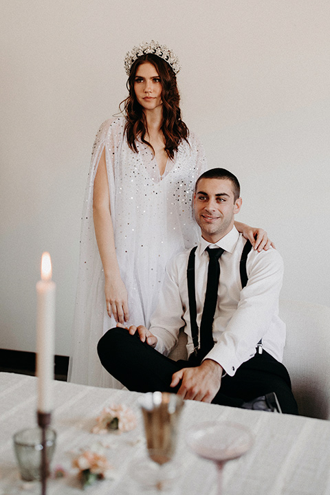 Rim-Rock-Ranch-Shoot-groom-sitting-bride-standing-bride-with-crown-on-and-a-sheer-bohemian-dress-with-crsystals-and-flutter-sleeves-groom-in-a-white-shirt-black-pants-and-black-suspenders