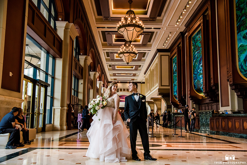 Hyatt-San-Diego-wedding-bride-and-groom-in-lobby-with-dogs-the-bride-is-in-a-blush-toned-ballgown-and-the-groom-in-a-black-shawl-lapel-tuxedo