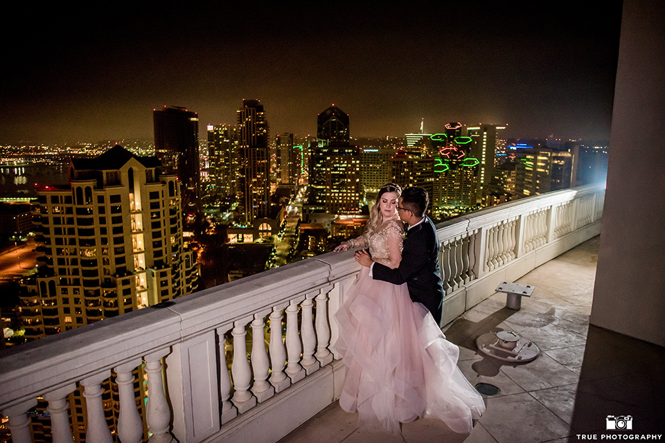 Hyatt-San-Diego-wedding-bride-and-groom-overlooking-city-at-night-the-bride-is-in-a-blush-toned-ballgown-and-the-groom-in-a-black-shawl-lapel-tuxedo