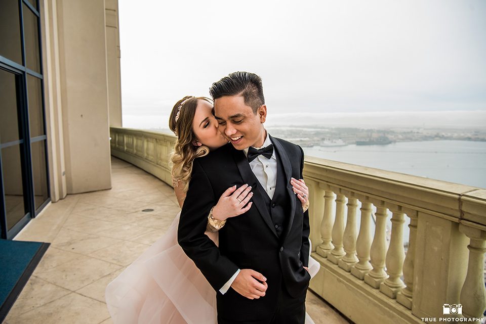 Hyatt-San-Diego-wedding-bride-hugging-groom-from-behind-the-bride-is-in-a-blush-toned-ballgown-and-the-groom-in-a-black-shawl-lapel-tuxedo
