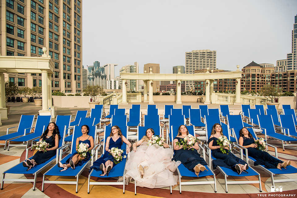 Hyatt-San-Diego-wedding-bridesmaids-on-pool-loungers-in-blue-gowns