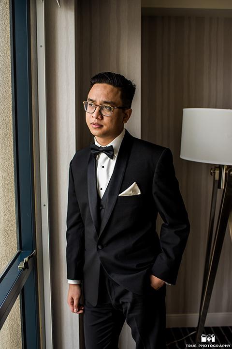 Hyatt-San-Diego-wedding-groom-looking-out-window-in-a-black-shawl-lape-tuxedo