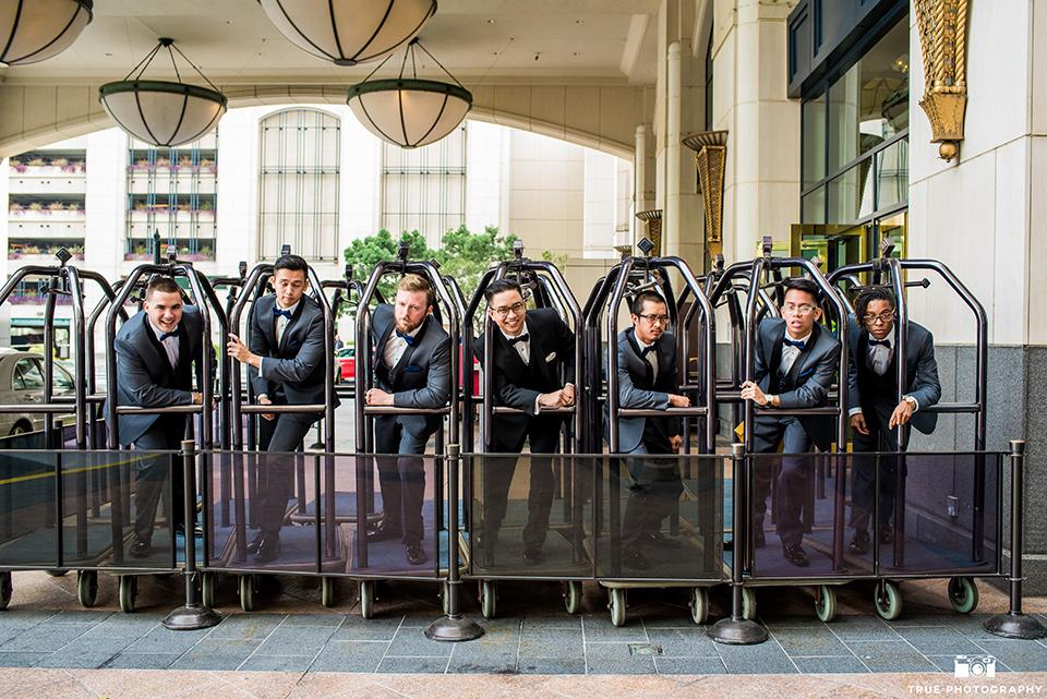 Hyatt-San-Diego-wedding-groomsmen-on-suitcase-carts-the-groom-in-a-black-shawl-lapel-tuxedo-the-groomsmen-in-grey-shalw-lapel-tuxedos