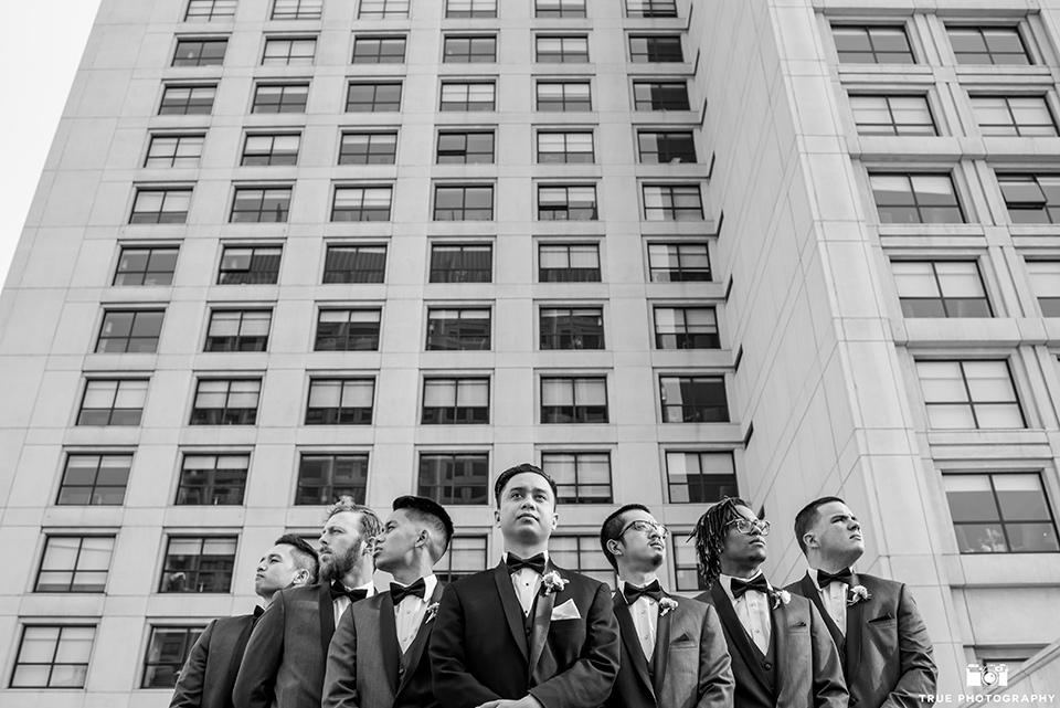 Hyatt-San-Diego-wedding-groomsmen-outside-venue-the-groom-in-a-black-shawl-lapel-tuxedo-the-groomsmen-in-grey-shalw-lapel-tuxedos