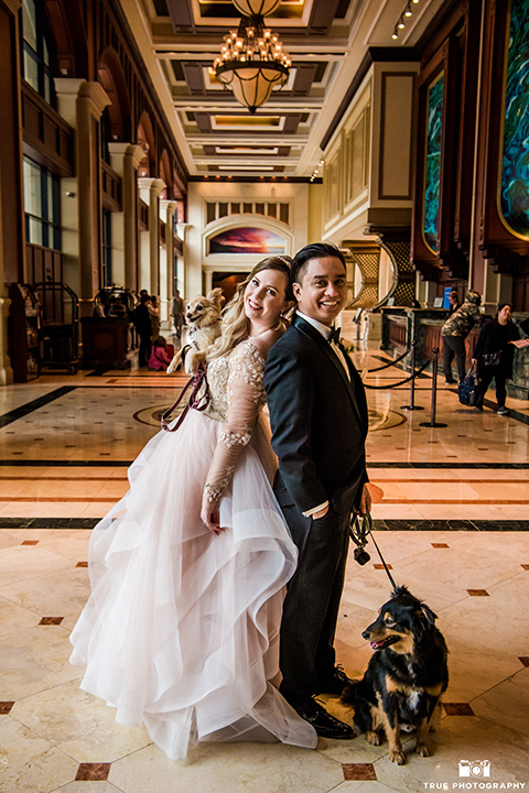 hyatt-san-diego-wedding-bride-and-groom-in-lobby-with-pets-the-bride-in-a-blush-ballgown-and-the-groom-in-a-black-tuxedo