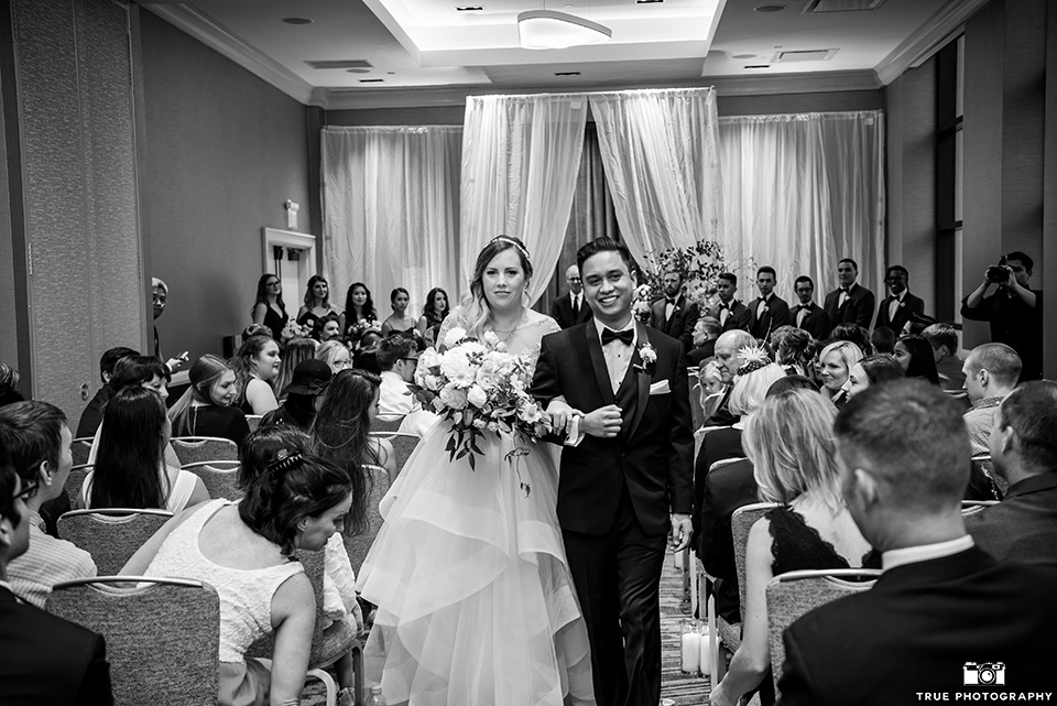 hyatt-san-diego-wedding-bride-and-groom-walking-down-aisle-the-bride-is-in-a-blush-toned-ballgown-and-the-groom-in-a-black-shawl-lapel-tuxedo