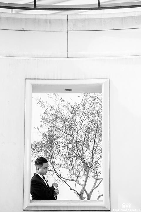 hyatt-san-diego-wedding-bride-looking-at-watch-in-a-black-shawl-lapel-tuxedo