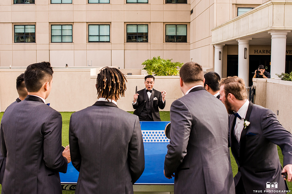 hyatt-san-diego-wedding-groomsmen-looking-at-grrom-playing-ping-pong-the-groom-in-a-black-shawl-lapel-tuxedo-the-groomsmen-in-grey-shalw-lapel-tuxedos