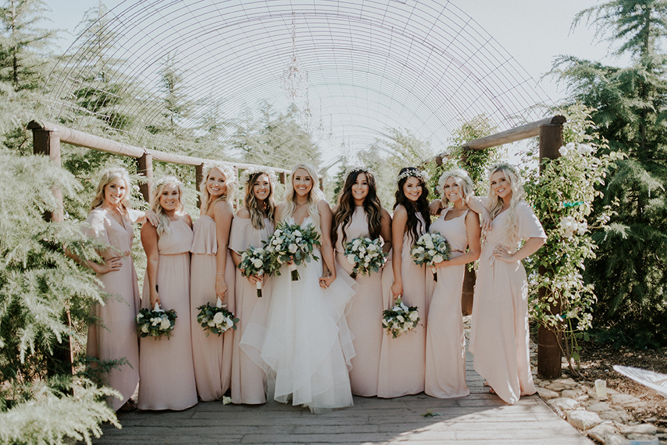 serendiity-gardens-bridesmaids-bride-in-a-tulle-ball-gown-with-straps-groom-in-grey-suit-with-brown-susenders-bridesmaids-in-pink-dresses