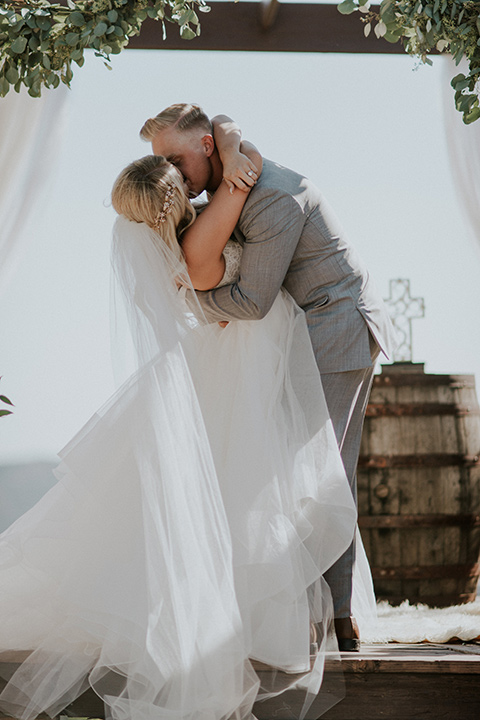serendiity-gardens-first-kiss-bride-in-a-tulle-ballgown-with-straps-groom-in-a-grey-suit-with-brown-suspenders