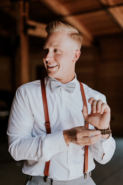 serendiity-gardens-groom-with-suspenders-alone-groom-in-a-grey-suit-with-brown-suspenders