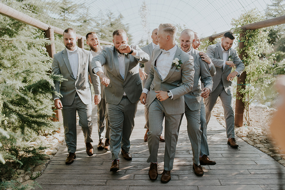 serendiity-gardens-groomsmen-walking-all-in-grey-suits-with-brown-suspenders