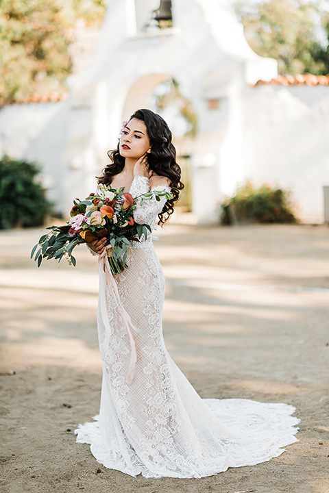 Olivas-Adobe-spanish-inspired-shoot-bride-alone-touching-her-neck-wearing-a-lace-form-fitting-gown-with-off-the-shoulder-detailing-and-long-sleeves