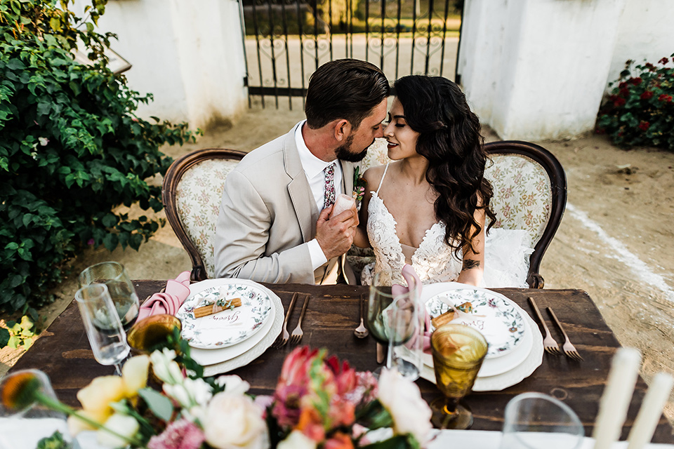 Olivas-Adobe-spanish-inspired-shoot-bride-and-groom-at-sweetheart-table-bride-in-a-spanish-inspired-lace-dress-and-groom-in-a-tan-suit