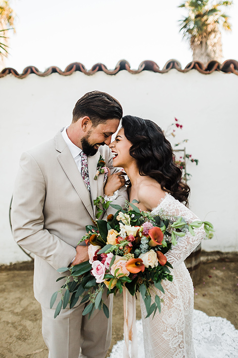 Olivas-Adobe-spanish-inspired-shoot-bride-and-groom-laughing-bride-wearing-a-lace-form-fitting-gown-with-off-the-shoulder-detailing-and-long-sleeves-groom-wearing-a-tan-suit-with-a-white-floral-neck-tie