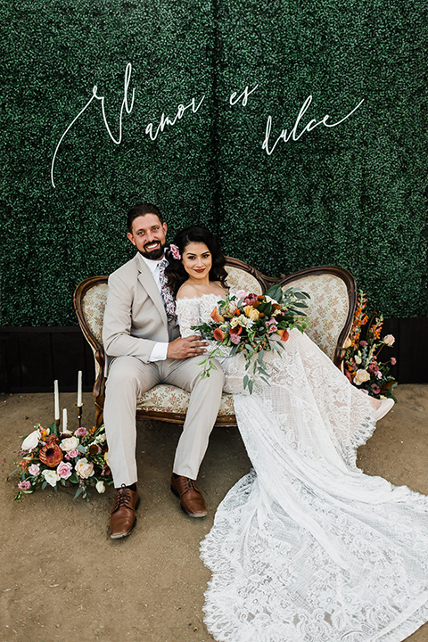 Olivas-Adobe-spanish-inspired-shoot-bride-and-groom-sitting-bride-wearing-a-lace-form-fitting-gown-with-off-the-shoulder-detailing-and-long-sleeves-groom-wearing-a-tan-suit-with-a-white-floral-neck-tie