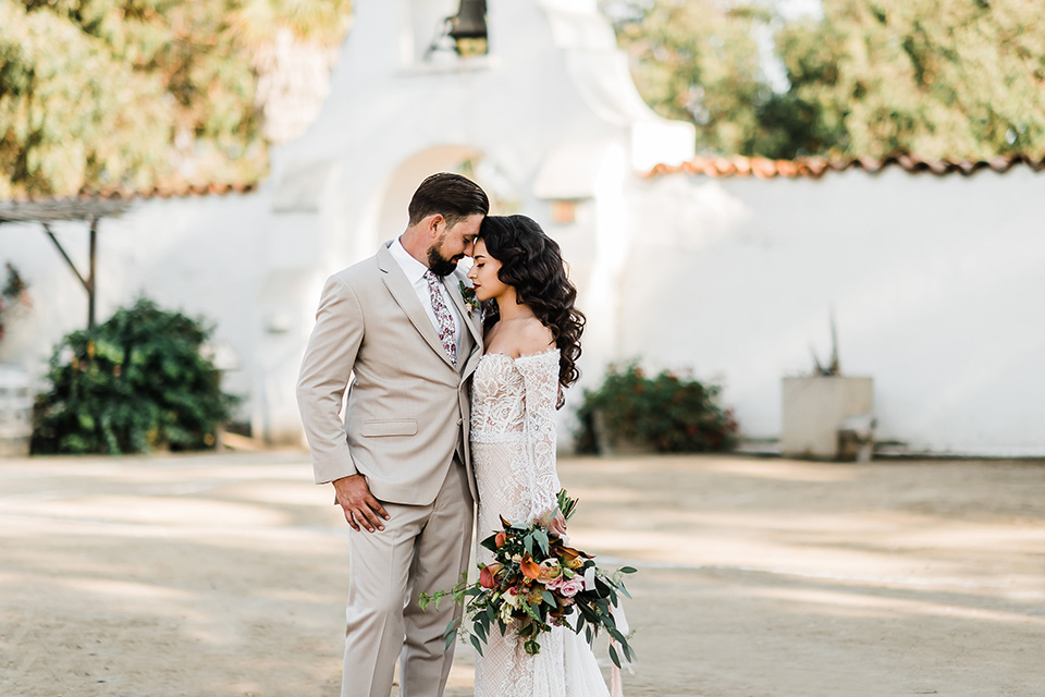 Olivas-Adobe-spanish-inspired-shoot-bride-and-groom-touching-heads-bride-in-a-spanish-inspired-lace-dress-with-long-sleeves-and-groom-in-a-tan-suit-with-a-floral-tie