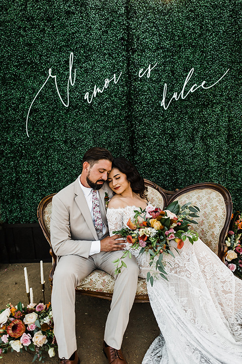 Olivas-Adobe-spanish-inspired-shoot-bride-resting-on-groom-bride-wearing-a-lace-gown-with-sleeves-and-holding-a-large-bouquet-of-flowers-groom-wearing-a-tan-suit-with-a-floral-tie