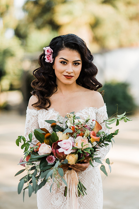 Olivas-Adobe-spanish-inspired-shoot-close-up-on-bride-wearing-a-lace-gown-with-sleeves-and-holding-a-large-bouquet-of-flowers