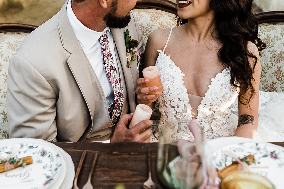 Olivas-Adobe-spanish-inspired-shoot-close-up-on-coule-at-sweetheart-table-bride-in-a-spanish-inspired-lace-dress-with-long-sleeves-and-groom-in-a-tan-suit-with-a-floral-tie