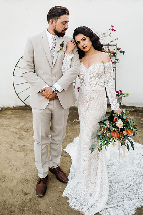 Olivas-Adobe-spanish-inspired-shoot-couple-looking-serious-bride-wearing-a-lace-gown-with-sleeves-and-holding-a-large-bouquet-of-flowers-groom-wearing-a-tan-suit-with-a-floral-tie