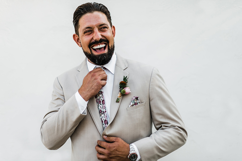 Olivas-Adobe-spanish-inspired-shoot-groom-laughing-in-a-tan-suit-with-a-floral-tie