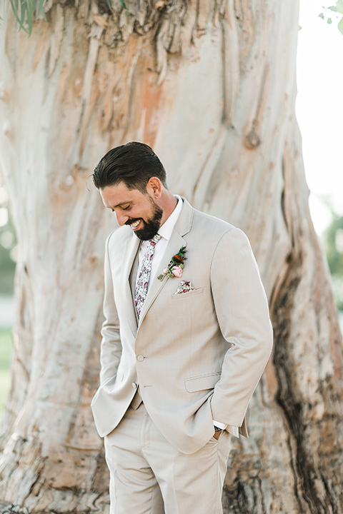 Olivas-Adobe-spanish-inspired-shoot-groom-looking-down-wearing-a-tan-suit-with-a-white-floral-neck-tie
