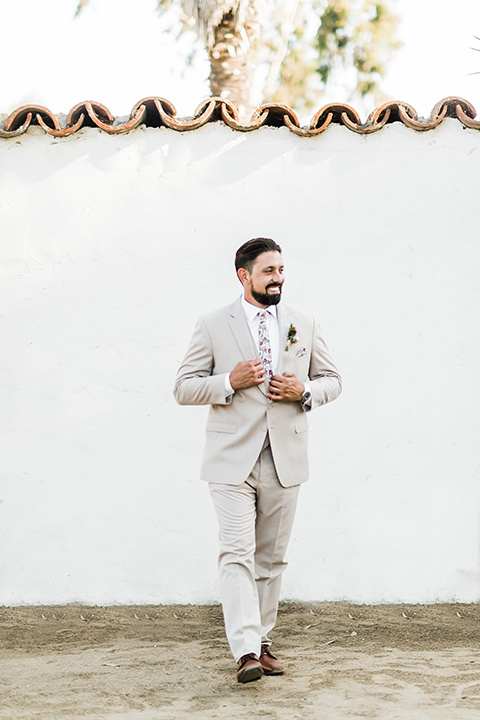 Olivas-Adobe-spanish-inspired-shoot-groom-walking-wearing-a-tan-suit-with-a-floral-tie