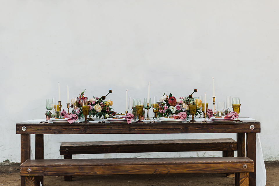 Olivas-Adobe-spanish-inspired-shoot-picnic-table-setting-with-wooden-table-and-white-linens-and-tall-candles
