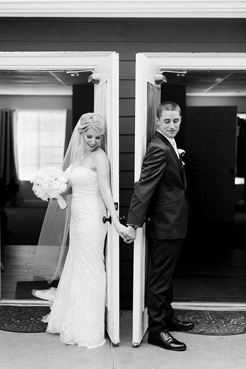 tropical-wedding-at-the-grand-tradition-bride-and-groom-backs-turned-to-eachother-the-bride-in-a-trumpet-style-gown-with-a-stapless-neckline-and-the-groom-in-a-navy-suit-with-an-ivory-tie
