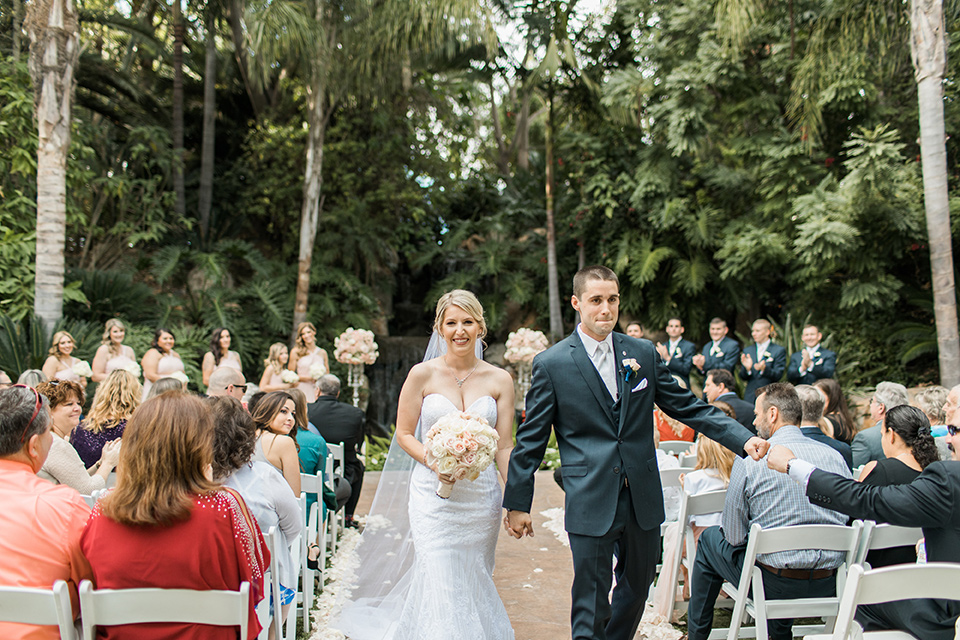 tropical-wedding-at-the-grand-tradition-bride-and-groom-walking-down-aisle-the-bride-was-in-a-trumpet-style-gown-with-a-strapless-neckline-and-the-groom-is-a-navy-suit-with-ivory-tie