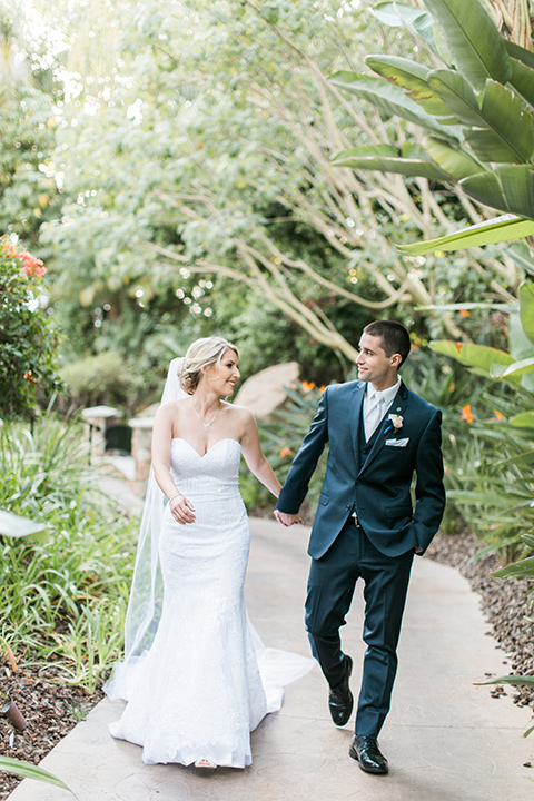 tropical-wedding-at-the-grand-tradition-bride-and-groom-walking-the-bride-in-a-trumpet-style-gown-with-a-sweetheart-neckline-the-groom-in-a-navy-blue-suit