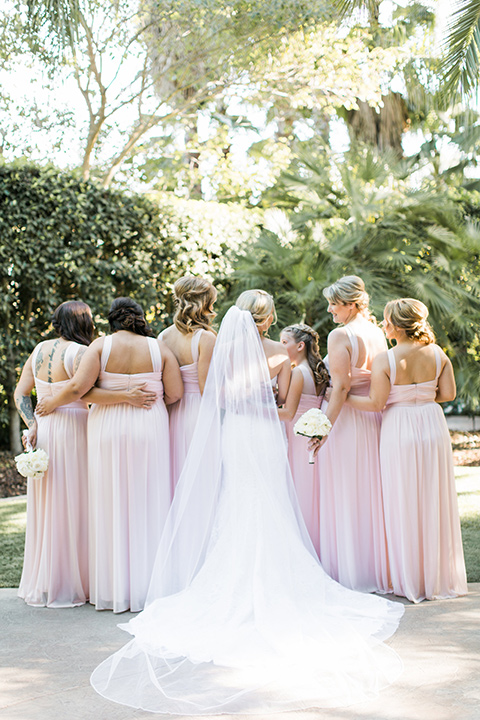 tropical-wedding-at-the-grand-tradition-bridesmaids-back-turned-to-camera-the-bridesmaids-in-pink-gowns-and-the-bride-in-a-white-trumpet-style-gown