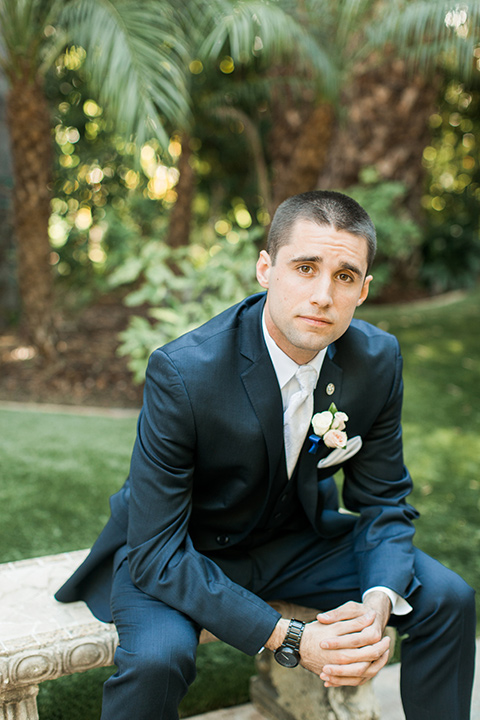 tropical-wedding-at-the-grand-tradition-groom-sitting-in-a-navy-suit-and-an-ivory-tie