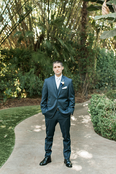 tropical-wedding-at-the-grand-tradition-groom-standing-in-a-navy-suit-and-an-ivory-tie
