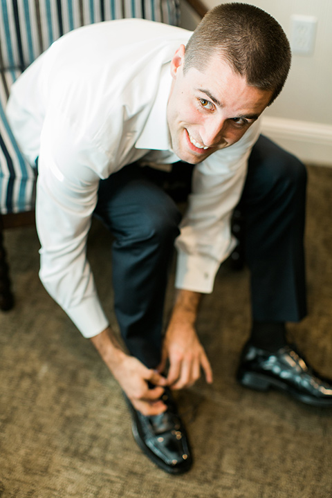 tropical-wedding-at-the-grand-tradition-groom-tying-shoes