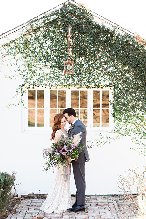 triunfo-creek-vineyards-wedding-bride-and-groom-outside-with-ivy-in-background-bride-wearing-a-flowing-ivory-and-blush-gown-with-straps-and-a-sweetheart-neckline-groom-in-a-charcoal-grey-suit-with-a-lack-bowtie