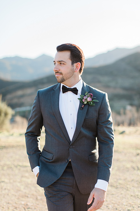 triunfo-creek-vineyards-wedding-groom-walking-groom-in-a-charcoal-grey-suit-with-a-lack-bowtie