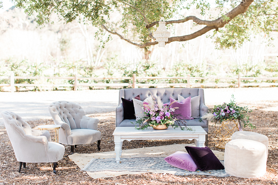 triunfo-creek-vineyards-wedding-outdoor-furniture-with-big-fluffy-purple-pillows-and-rugs-in-various-tones