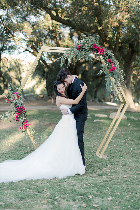 milagro-winery-bride-and-groom-at-ceremony-bride-in-a-tulle-ball-gown-groom-in-a-traditional-shawl-lapel-tuxedo-with-black-bow-tie