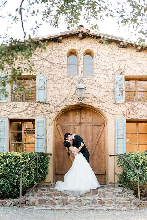 milagro-winery-bride-and-groom-by-building-kissing-bride-in-a-tulle-ball-gown-groom-in-a-traditional-shawl-lapel-tuxedo-with-black-bow-tie