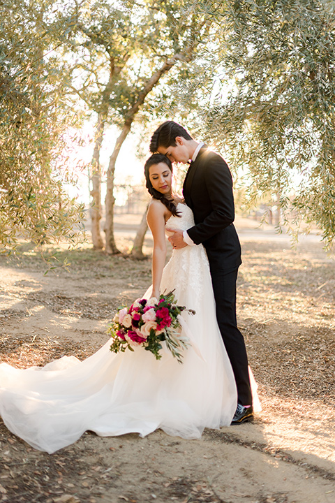 milagro-winery-bride-and-groom-touching-heads-bride-in-a-tulle-ball-gown-groom-in-a-traditional-shawl-lapel-tuxedo-with-black-bow-tie